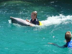 Chabelita op haar rug door het water.